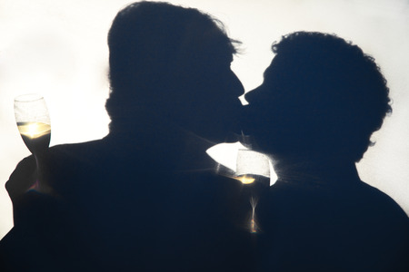 Silhouette of gay men kissing on their wedding day, holding champagne glasses behind an opaque screen.