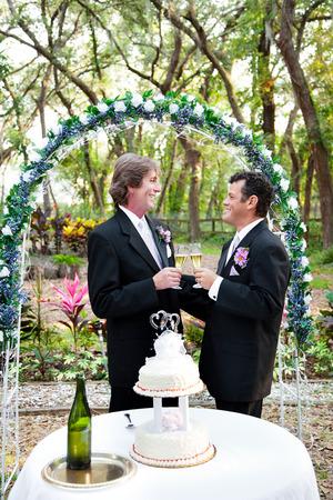 boda gay: Feliz pareja gay guapo brindando con champán bajo arco floral de la boda. Pastel de bodas con dos novios en primer plano.
