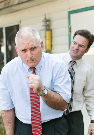 Businessman showing symptoms of flu or other illness such as ebola.  Worried friend and business colleague in background. photo