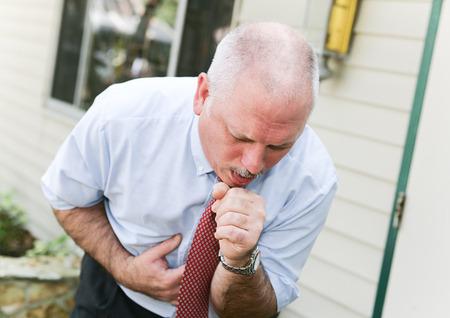 tosiendo: Hombre de negocios maduro con el pelo gris, se dobló con una mala tos de un resfriado, gripe o el ébola