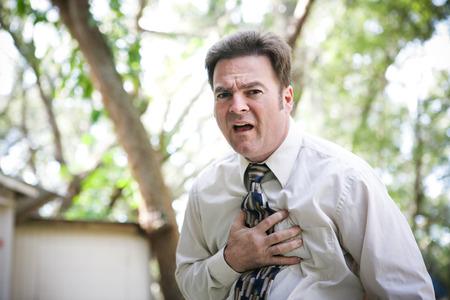 angina: El hombre de negocios que sufre en el pecho o est�mago dolor relacionado con ataque al coraz�n, angina de pecho, u otros illenss como la gripe o el �bola. Foto de archivo