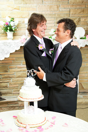 Two handsome gay men in tuxedos embrace with love at their wedding reception.  Wedding cake and rose petals in foreground. photo