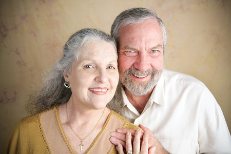 emphasis: Beautiful senior Christian couple.  She is wearing a cross and wedding.  Portrait illustrating traditional family values.  Slight vignette added for emphasis.