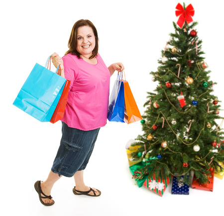 Pretty plus sized woman excited about bargain shopping for Christmas.  Full body isolatedo on white. photo