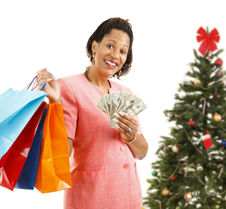 Beautiful African-american woman holding shopping bags and money.  Isolated on white, in front of a Christmas tree.   Stock Photo