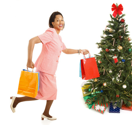 bargains: African-american female shopper running from one store to another for bargains on Christmas gifts.  Isolated on white.