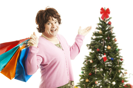fake christmas tree: Man dressed as woman going on a Christmas shopping spree, holding bags.  Isolated on white.