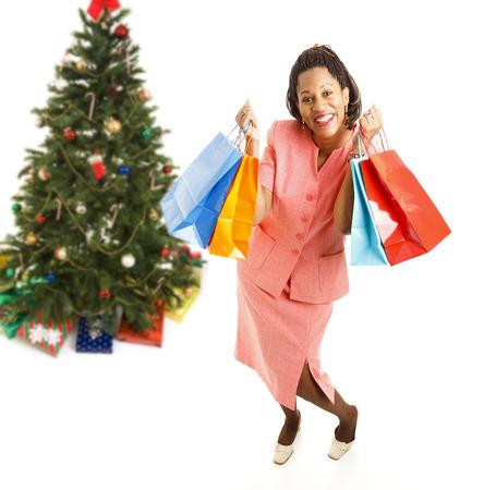 cornrows: Emocionado mujer afroamericana, sosteniendo bolsas de la compra. El cuerpo aislado en blanco con el �rbol de Navidad en el fondo. .