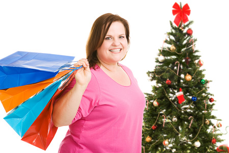 plus sized: Happy plus sized model holding shopping bags, standing in front of a Christmas tree.  Isolated on white.