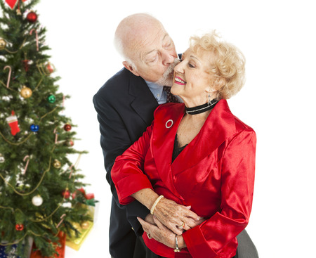 Senior couple dressed for the holidays.  Hes giving her a kiss on the cheek.  Isolated with Christmas tree in background.