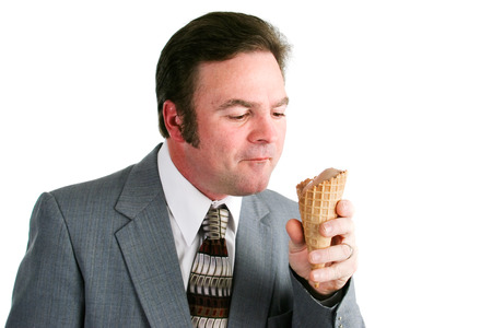 Man in business suit eating a chocolate ice cream waffle cone.  Isolated on white background