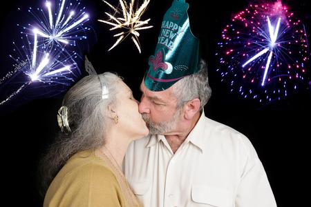 novios besandose: Pareja mayor hermosa en besos una fiesta de A�o Nuevo en el filo de la medianoche como los fuegos artificiales se apagan en el fondo. Foto de archivo