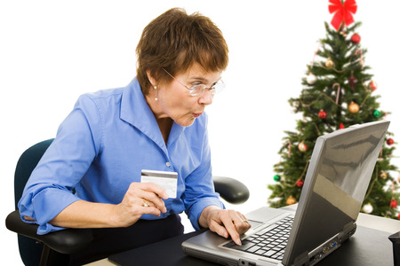 bargain for: Mature woman finds a bargain shopping online for Christmas presents.  Isolated on white. Stock Photo