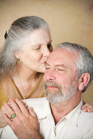 Beautiful senior woman gives her husband a loving kiss on the forehead.  Vignette added for dramatic effect.
