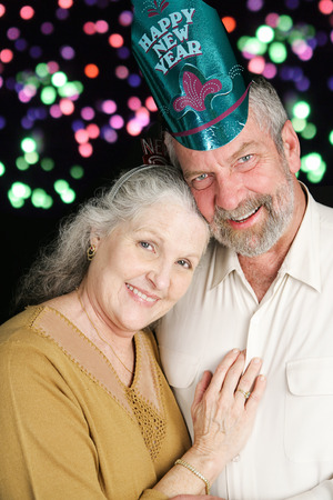 Beautiful couple in their sixties posing for a romantic portrait on New Years Eve.  Fireworks in the background.