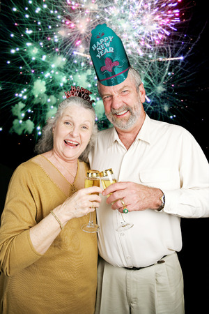 Senior couple a bit drunk at a New Year's Eve party with fireworks going off in the background photo