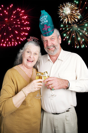 Senior couple a bit drunk on champagne at a New Years Eve party.  Black background.