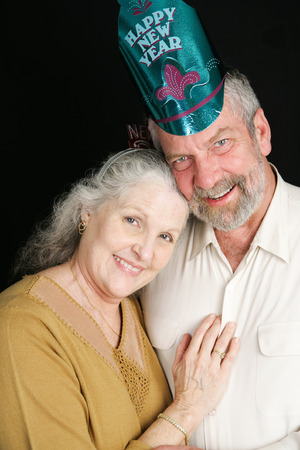 Beautiful couple in their sixties posing for a romantic portrait on New Year's Eve.  Black background. photo