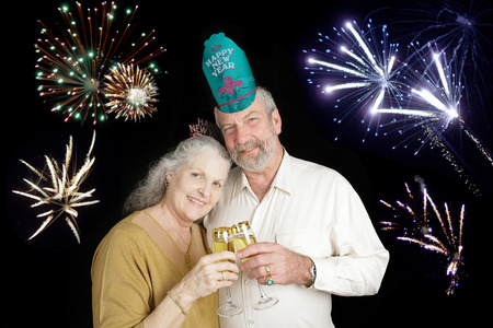 Beautiful senior couple celebrating a Happy New Year with a champagne toast, while fireworks go off in the background. photo