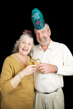 Senior couple a bit drunk on champagne at a New Year's Eve party.  Black background. photo