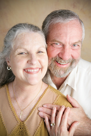 Portrait of beautiful happy senior couple in a traditional Christian marriage.  She is wearing a cross. photo