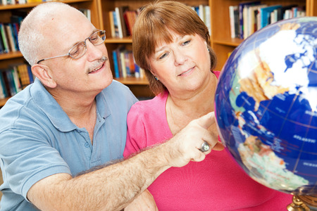 overweight students: Adult students in library using a globe to study geography. Stock Photo