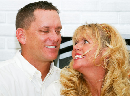 thirties: Beautiful husband ans wife in their thirties, laughing together at home in front of the fireplace.