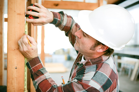 Carpenter taking measurements on a construction site. Stockfoto