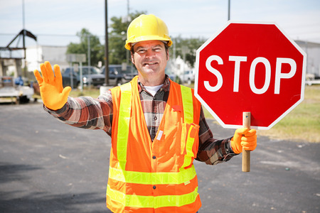 Friendly construction worker in the road holding up a stop sign. Foto de archivo