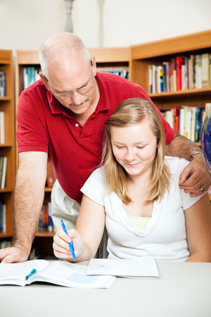 Father or teacher helping a teenage student at the library. Reklamní fotografie