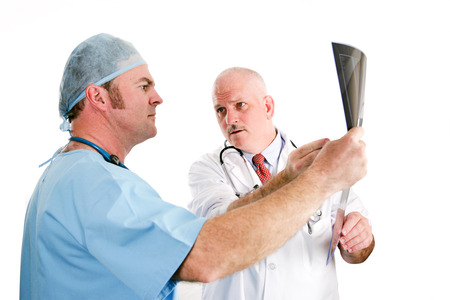 intern: Doctors discussing x-ray results.  Focus on the older doctor pointing out a problem to his younger intern.  Isolated on white.