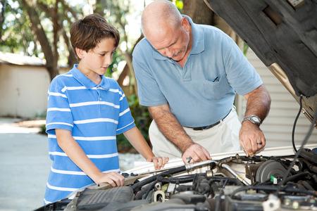 Father teaching his son basic auto maintenance. photo