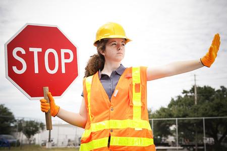 señales de transito: Mujer aprendiz construcción la celebración de una señal de stop y dirigir el tráfico. Foto de archivo