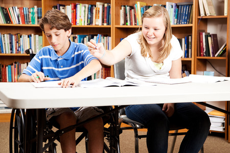 Teen boy and girl goofing around in the library.  The boy is disabled in a wheelchair. photo
