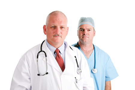 labcoat: Mature doctor and younger, surgical intern.  Medical team with serious expressions.  Isolated on white.