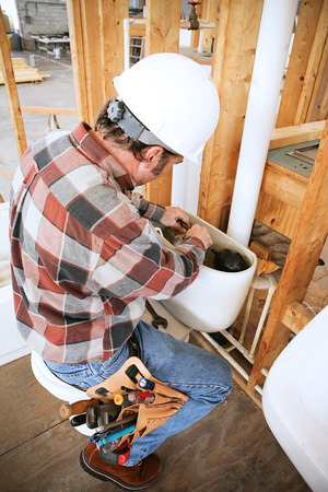 Plumber installing a toilet on a construction site. photo