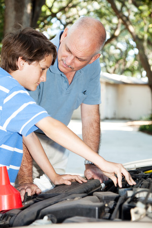 Father teaching his son how to do auto repairs, oil change, etc. photo