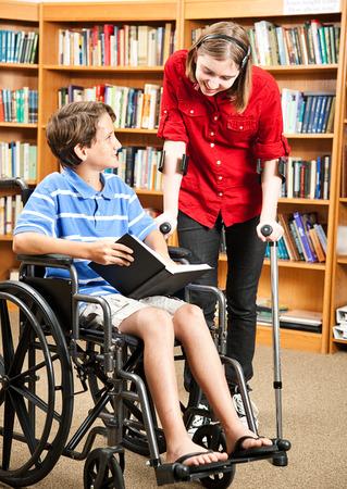 discapacidad: Dos ni�os con discapacidad en la biblioteca de la escuela, uno en una silla de ruedas y otro con muletas.