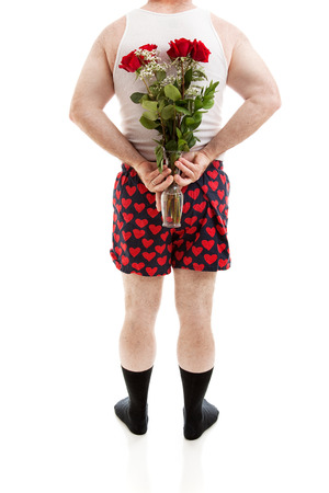 Guy in heart boxers and undershirt holding a bouquet of red roses for Valentines Day behind his back.  Isolated on white.