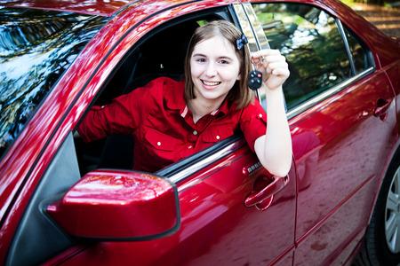 Adolescente avec sa licence de pilote au volant d'une nouvelle voiture et maintenant les touches. Banque d'images