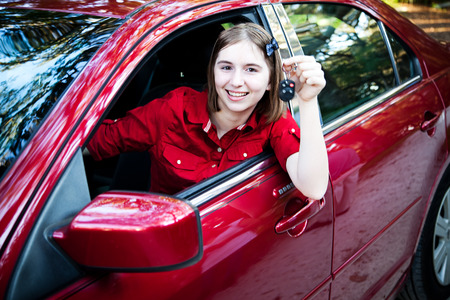 Teenage girl with her drivers license driving a new car and holding keys.