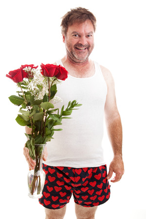 Scruffy looking middle aged guy in his underwear holding a bouquet of red roses for Valentines Day.  Isolated on white.