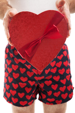 Guy in his heart boxer shorts giving a valentines day box of chocolates to you.,