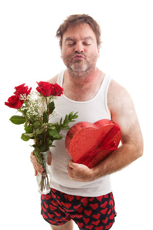 wife beater: Scruffy middle aged man in his underwear with flowers and candy for Valentines Day, puckering up for a kiss.  Isolated on white.