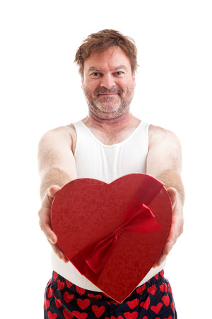 Scruffy middle aged man giving you a heart shaped box of candy for Valentines Day.  Isolated on white Reklamní fotografie