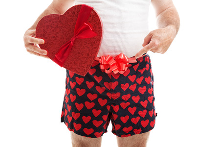 wife beater: Guy in his underwear with a Valentines Day gift and a bow around his underwear, pointing toward his crotch.  Isolated on white. Stock Photo