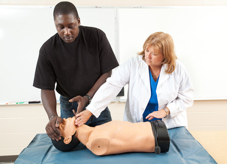 chest compression: Adult student learning CPR from a medical doctor, using a state-of-the-art dummy.