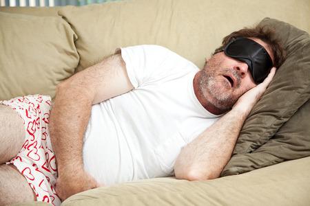 borracho: Hombre perezoso en casa en su ropa interior, durmiendo en el sofá y los ronquidos. Foto de archivo