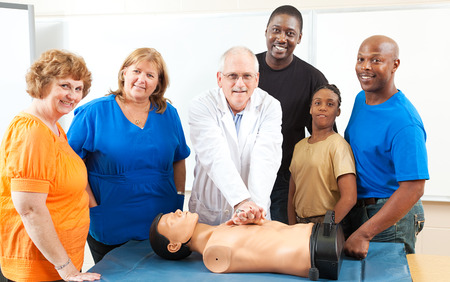 chest compression: Adult education class learning CPR first aid from a doctor.