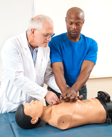 Doctor helping an adult student learn CPR. photo